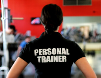 A woman standing defines that she is a personal trainer, at tranceform fitness which is a leading gym and fitness club in Pune has certified trainers